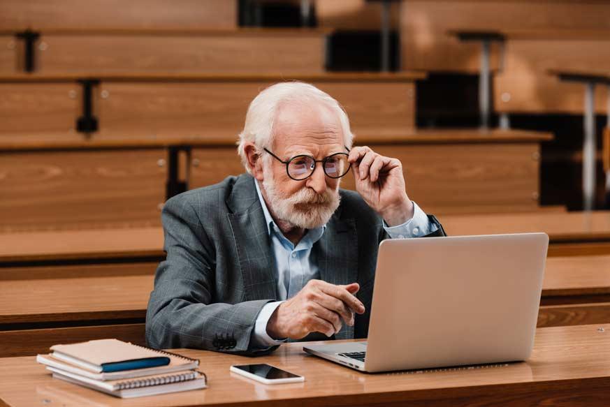 Professor Looking at Laptop - PE Power Exam